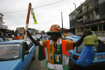 An Ivory Coast fan dressed in the colours of the Ivory Coast flag cheers before their 2010 World Cup soccer match against Brazil, in Abidjan