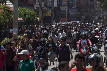 People evacuate onto a street minutes after a fresh 7.3 earthquake struck, in central Kathmandu
