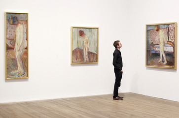 """Holden of the Tate poses with three paintings of Edvard Munch's """"Weeping Woman"""" series at the Tate Modern in London's Southbank"""