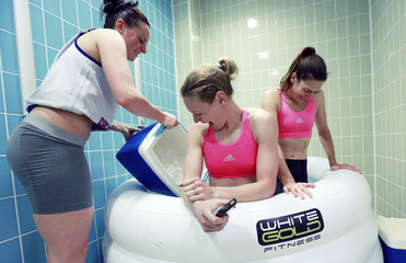 Rose Anderson adds ice to the bath which team mates Rachael Vanderwal and Natalie Stafford, of Britain's Team GB women's basketball team, use to regenerate muscle tissue after practice, in a training camp prior to the London 2012 Olympic Games in Guildford