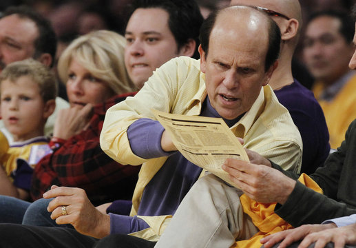 Milken Institute chairman Michael Milken looks at a line up sheet as he sits courtside at the NBA basketball game between the Los Angeles Lakers and the Chicago Bulls in Los Angeles