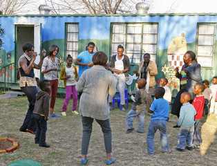 U.S. first lady Michelle Obama and family dance with children and caretakers as they visit the Emthonjeni Community Center in Zandspruit  Township