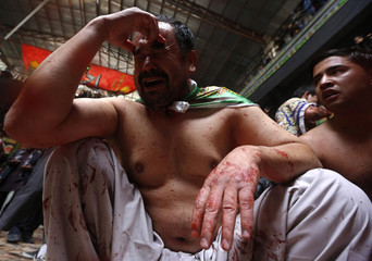 Afghan Shi'ite Muslim man bleeds after flagellating himself with chains during an Ashura procession in Kabul