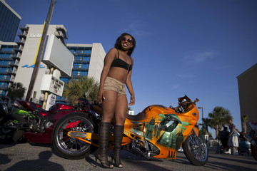 "Sierra ""Lovely Amazin"" Redd of Greensboro, North Carolina, poses for bikers by a custom Suzuki Katana on Ocean Boulevard during the 2015 Atlantic Beach Memorial Day BikeFest in Myrtle Beach"