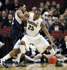 Johnson of Purdue is guarded by Conley of Saint Peter's during their NCAA basketball game in Chicago