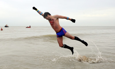 A man dressed to look like Superman plays in the water as people take their first bath in the North Sea to celebrate the arrival of the new year in Ostende