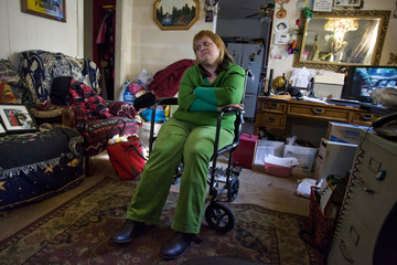 Ana Casas Wilson sits in the living room of her home which is currently under foreclosure