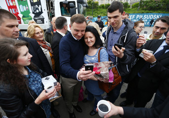 Duda, presidential candidate of the Law and Justice Party (PiS), poses for a picture with passerbys outside a subway station in central Warsaw