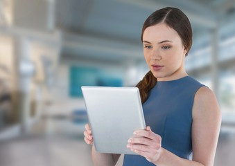 Businesswoman holding tablet in bright space hall