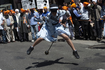 A Sikh dances with a mace as he demonstrates Gatka, a traditional form of martial arts, during the annual Sikh Day Parade in New York