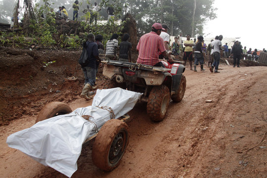 Surinamese and Brazilian rescue workers transport the body of one of seven wildcat miners who died when the 20-meter-high dirt wall of a gold mine collapsed, at Money Hill