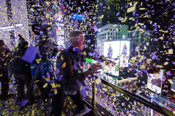 Confetti engineer Norm Larsen tosses confetti onto revellers from the roof of the Marriott Marquis hotel during New Year's Eve celebrations in Times Square in New York