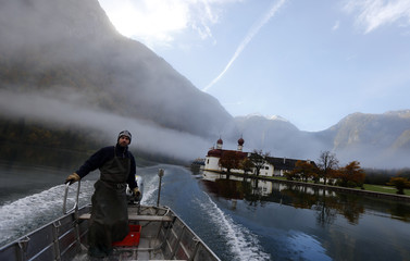 German fisherman Amort fishes for char to make traditional smoked fish at lake Koenigssee