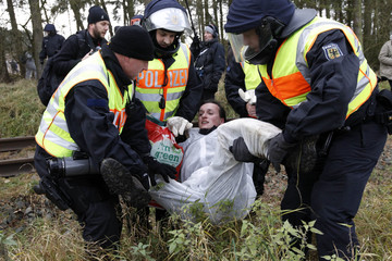 German police officers arrest anti-nuclear protesters who removed stones from the railway tracks near Lemgrabe
