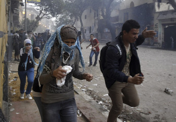 Protesters run from tear gas released by riot police during clashes after a rally to mark the one-year anniversary of fatal clashes at Mohamed Mahmoud street in Cairo