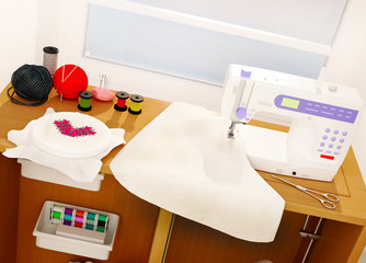 White sewing machine, embroidery, details and cloth.