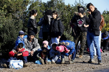 Syrian refugees wait on a roadside near a beach in the western Turkish coastal town of Dikili, Turkey, after Turkish Gendarmes prevented them from sailing off for the Greek island of Lesbos by dinghies