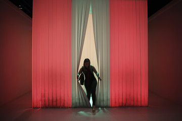 "A woman walks through curtains in an installation called ""Immersion"", at the exhibition ""O nome da Cor"" (The name of Colour) in Sao Paulo"
