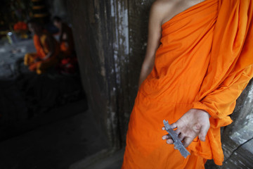 Buddhist monk shows a piece of shrapnel found at the 11th-century Preah Vihear temple on the border between Thailand and Cambodia