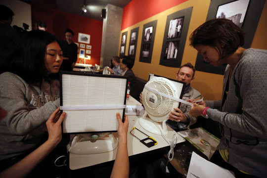 People assemble home made air purifiers during a workshop organized by Smart Air Filters at a local coffee shop in Shanghai