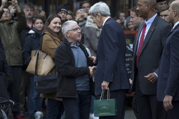 United States Secretary of State John Kerry speaks with a man after departing Fassbender and Rausch chocolate store during an unscheduled stop in Berlin
