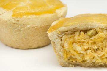 Two traditional Brazilian mini chicken pie called empada with one cut close