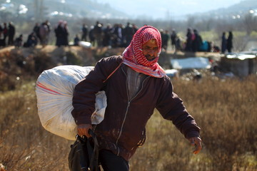 An internally displaced Syrian fleeing advancing pro-government Syrian forces carries his belongings near the Syrian-Turkish border after being given permission by the Turkish authorities to enter Turkey, in Khirbet Al-Joz