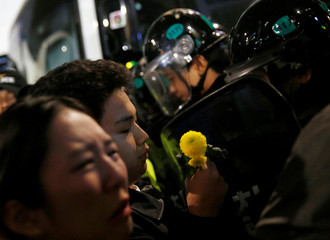 A protester holds a flower in front of riot police who block protesters on a road near the presidential Blue House during the protesters' march calling South Korean President Park to step down in Seoul