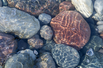 Ripples of the crystal clear shallow water surface, on a stony beach of Lake Huron, Ontario, Canada.
