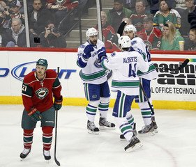 Canucks left wing Higgins celebrates his goal with teammates as Wild center Brodziak skates past during the second period of their NHL hockey game in St. Paul, Minnesota
