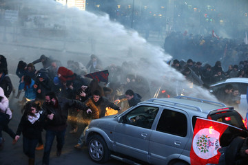 Anti-government protesters run as riot police fires a water cannon during a demonstration in Istanbul