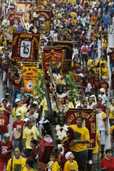 Devotees walk carrying replicas of the Black Nazarene during a procession in Manila
