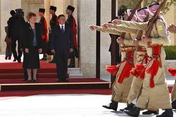 Jordan's King Abdullah and Finland's President Halonen review Bedouin honour guards upon her arrival at the Royal Palace in Amman