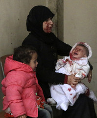 A woman holds her crying baby in a hospital in Aleppo's al-Sakhour district