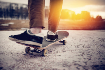 Man male skateboarder on a skateboard is riding in the sunset on the road, close-up. Concept street sport in holey boots.