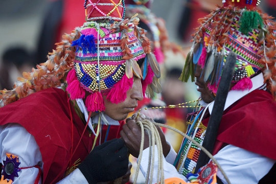 "An Andean dancer wearing a feathered hat kisses a rosary before the beginning of celebrations in honor of the Lord of ""Qoyllur Rit'i"" near the town of Tayankani in Cuzco"