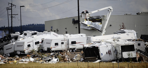 Power utility crews work to restore power to Camping World amid overturned trailers after two tornadoes touched down Arizona
