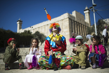 A Jewish settler dressed as a clown juggles next to children as the Tomb of the Patriarchs is seen in the background, during Purim in Hebron