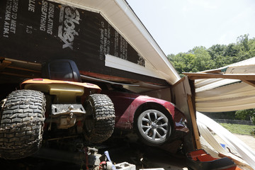 A car and a lawnmower stick out from the wall of a collapsed garage after flooding in Falling Rock