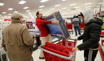 Store employee helps a customer with his TV purchase during the Black Friday sales event on Thanksgiving Day at Target in Chicago