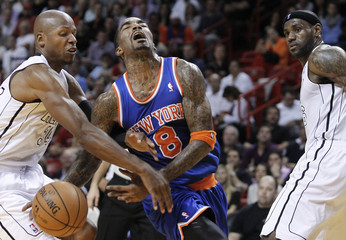 Miami Heat's Ray Allen fouls New York Knicks' J.R. Smith as the Heat's LeBron James looks on in the send half of their NBA basketball game in Miami, Florida