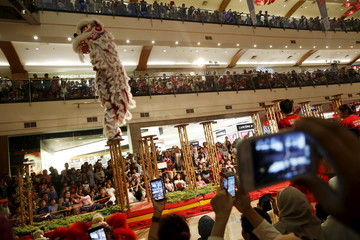 People watch and take pictures of a dragon dance performance during Chinese Lunar New Year celebrations at Pondok Indah Mall in Jakarta, Indonesia