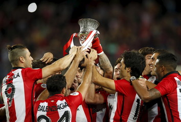 Athletic Bilbao's players raise up the Spanish Super Cup trophy after defeating Barcelona at Camp Nou stadium in Barcelona