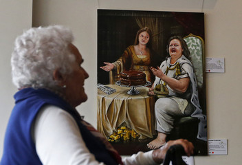 A woman looks at the painting 'The Banquet of Gina and Ginia' at the Bald Archy Prize exhibition in Sydney