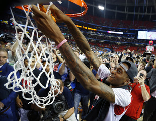 Injured Louisville Cardinals guard Ware cuts down the net after the Cardinals defeated the Michigan Wolverines in their NCAA men's Final Four championship basketball game in Atlanta