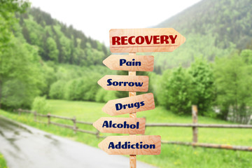 Rehabilitation concept. Wooden signboards pointing different directions to RECOVERY and ADDICTION on landscape background