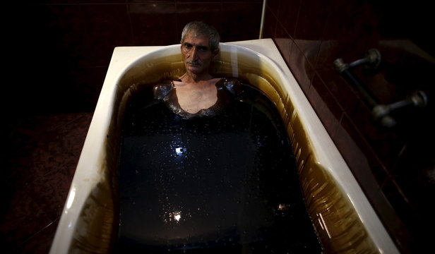 Man lies in a bathtub filled with crude oil during a health therapy session at Naftalan Health Center in Baku, Azerbaijan