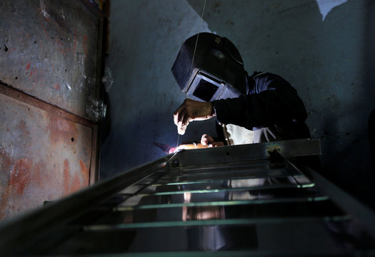 A worker welds steel pipes to make a counter at a steel furniture manufacturing unit in Ahmedabad