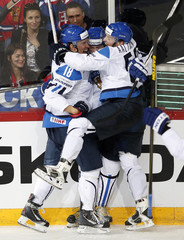 Finland's players celebrate their goal against Russia during their 2013 IIHF Ice Hockey World Championship preliminary round match at the Hartwall Arena in Helsinki