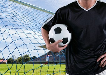 soccer player with the ball on his arm in front of the goal
